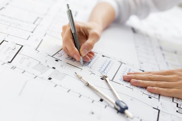 Une personne travaille sur un plan de maison