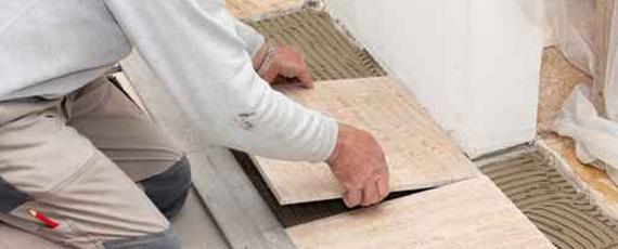 Un artisan pose du carrelage dans le cadre d'une rénovation de salle de bain